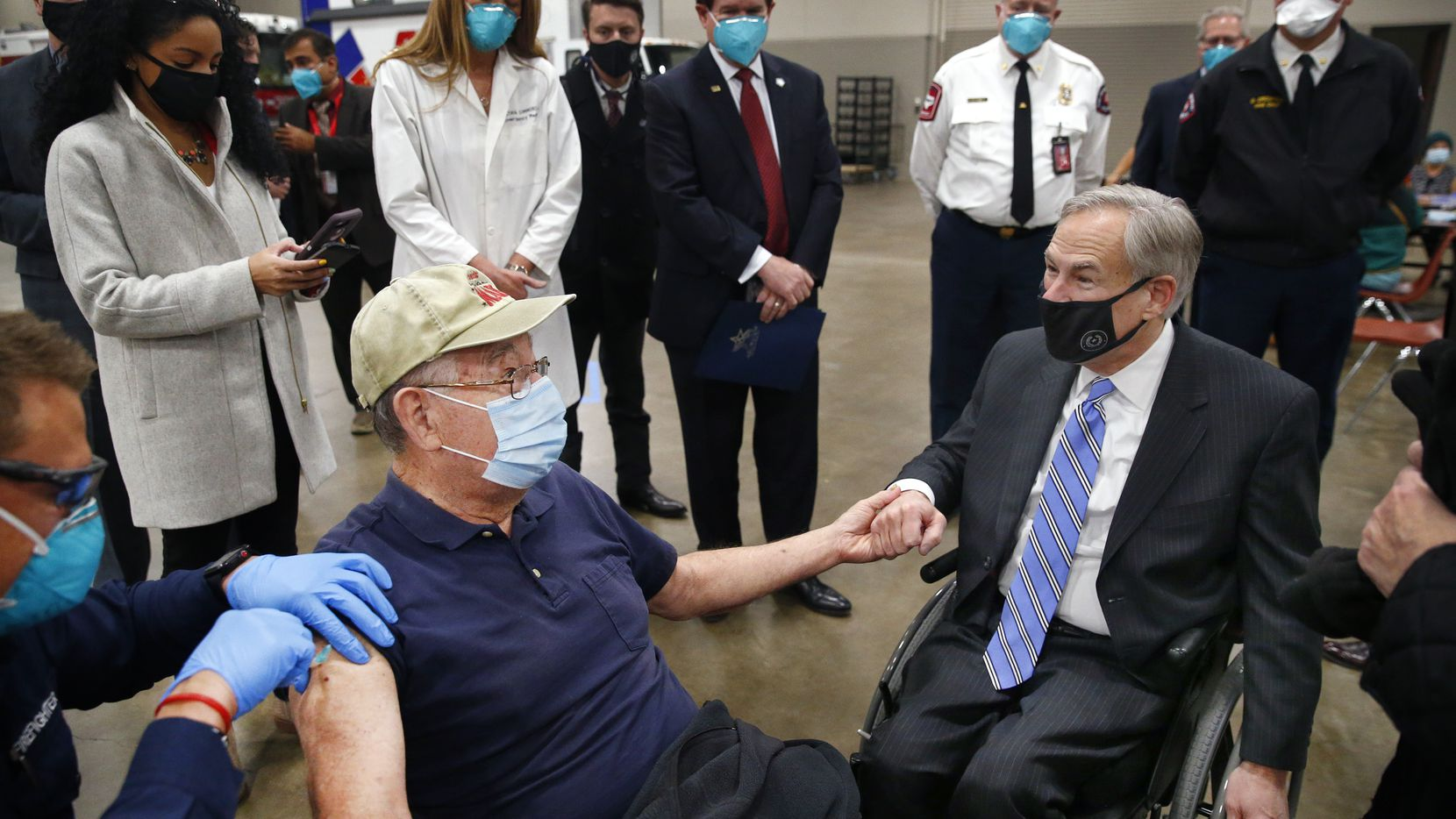 Texas Governor Greg Abbott (right) holds the hand of 86 yr-old Al Godfrey of Arlington as he receives his COVID-19 shot at a mass vaccination site inside Esports Stadium Arlington & Expo Center in Arlington, Texas, Monday, January 11, 2021. Earlier Abbott met with local and state officials for a briefing and then provided an update on COVID-19 vaccine efforts in Texas. (Tom Fox/The Dallas Morning News)