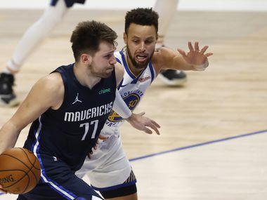 Mavericks guard Luka Doncic (77) drives by Warriors guard Stephen Curry (30) during the fourth quarter of play at American Airlines Center on Saturday, Feb. 6, 2021, in Dallas.