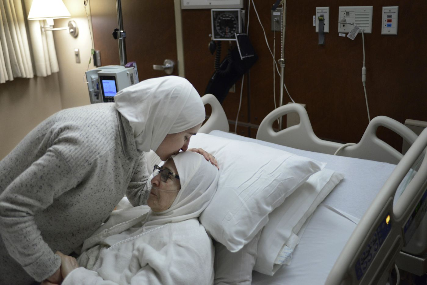 Nour Ulayyet left, comforts her mother Isaaf Jamal Eddin at Munster Community Hospital Saturday, Jan. 28, 2017, in Munster, Ind. Ulayyet of Valparaiso, Ind., said her sister, a Syrian living in Saudi Arabia who had a valid visa, was sent back after arriving from Riyadh at Chicago's O'Hare International Airport on Saturday and told she couldn't enter the U.S. to help care for their sick mother.