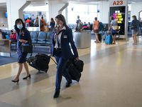American Airlines flight attendants walk along the concourse at DFW International Airport.