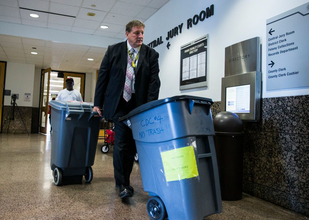 Large bins filled with questionnaires are wheeled out of the Central Jury Room after potential jurors for the Amber Guyger trial filled them out on Friday at the Frank Crowley Courts Building in Dallas.
