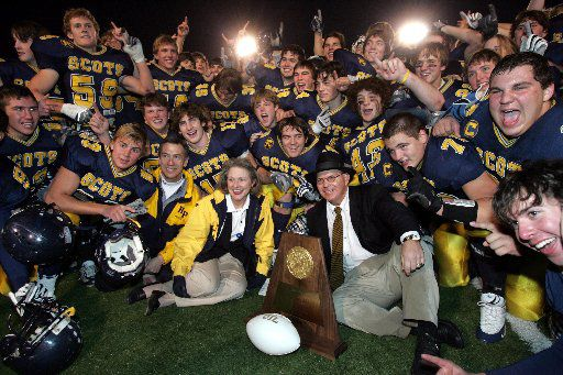 Highland Park players and staff and coach Randy Allen (center) pose with  the championship trophy on the field after the Scots 59-0 victory in the 4A Division I State High School Football Championship game at the Rose Stadium in Tyler, TX on Saturday, December 10, 2005.