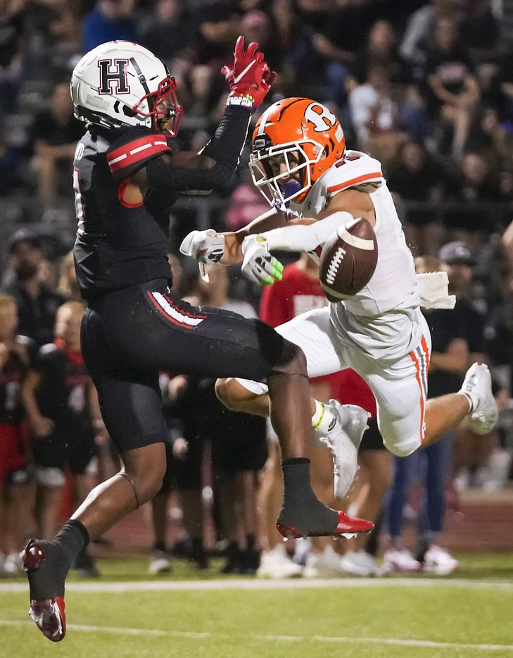 Rockwall defensive back Cadien Robinson (13) breaks up a pass intended for Rockwall-Heath wide receiver Jay Fair (1) during the second half of a District 10-6A high school football game at Wilkerson-Sanders Stadium on Friday, Sept. 24, 2021, in Rockwall.  Rockwall-Heath won the game 79-71 in double overtime.