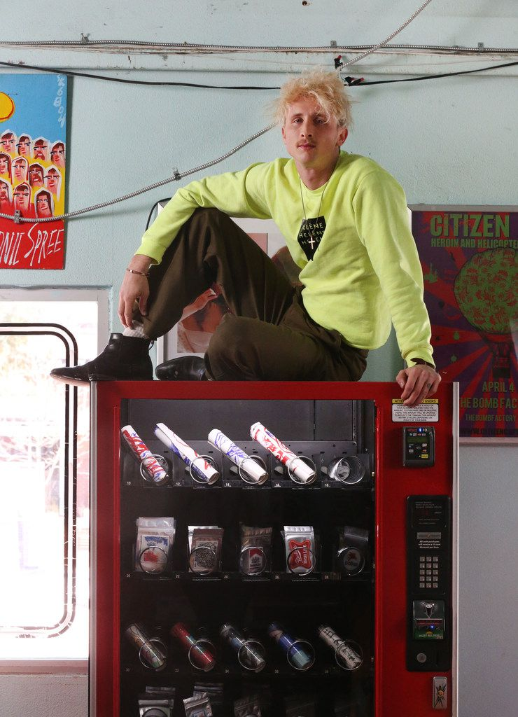 Artist Matthew Brinston poses for a photograph atop his art vending machine at Good Records in Dallas
