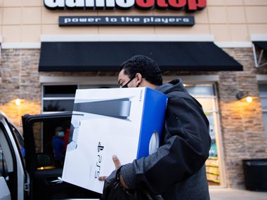 Brandon Lopez of Irving loads his new Playstation 5 in his car after waiting in line since 10 a.m. yesterday at the Timber Creek Crossing Gamestop location during Black Friday in Dallas on Friday, Nov. 27, 2020.