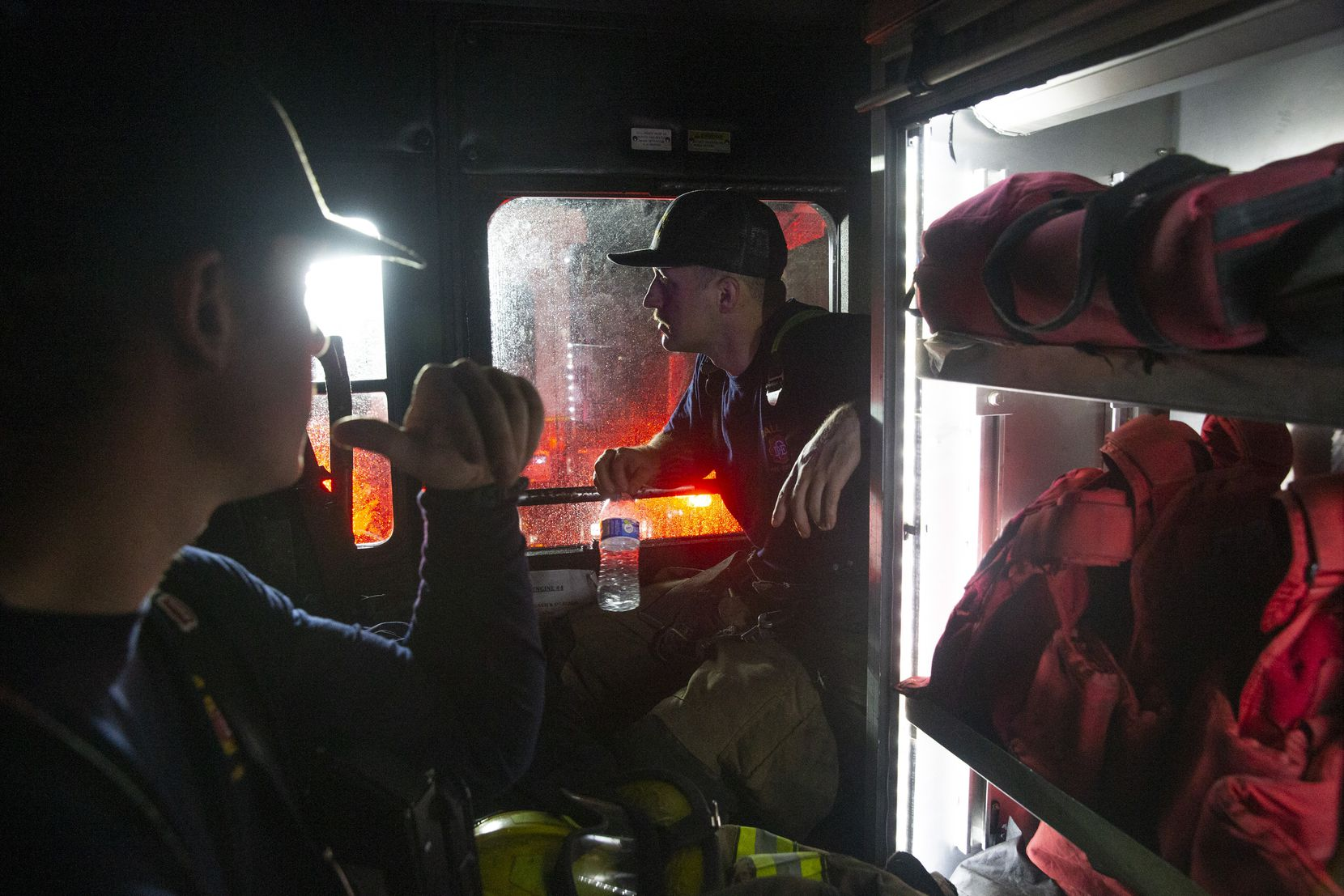 Dallas firefighters Chaz Ponder (right) and Josh Hamm wait out a second storm in Engine 43 a few hours after a tornado hit parts of northern Dallas on Sunday, Oct. 20, 2019.