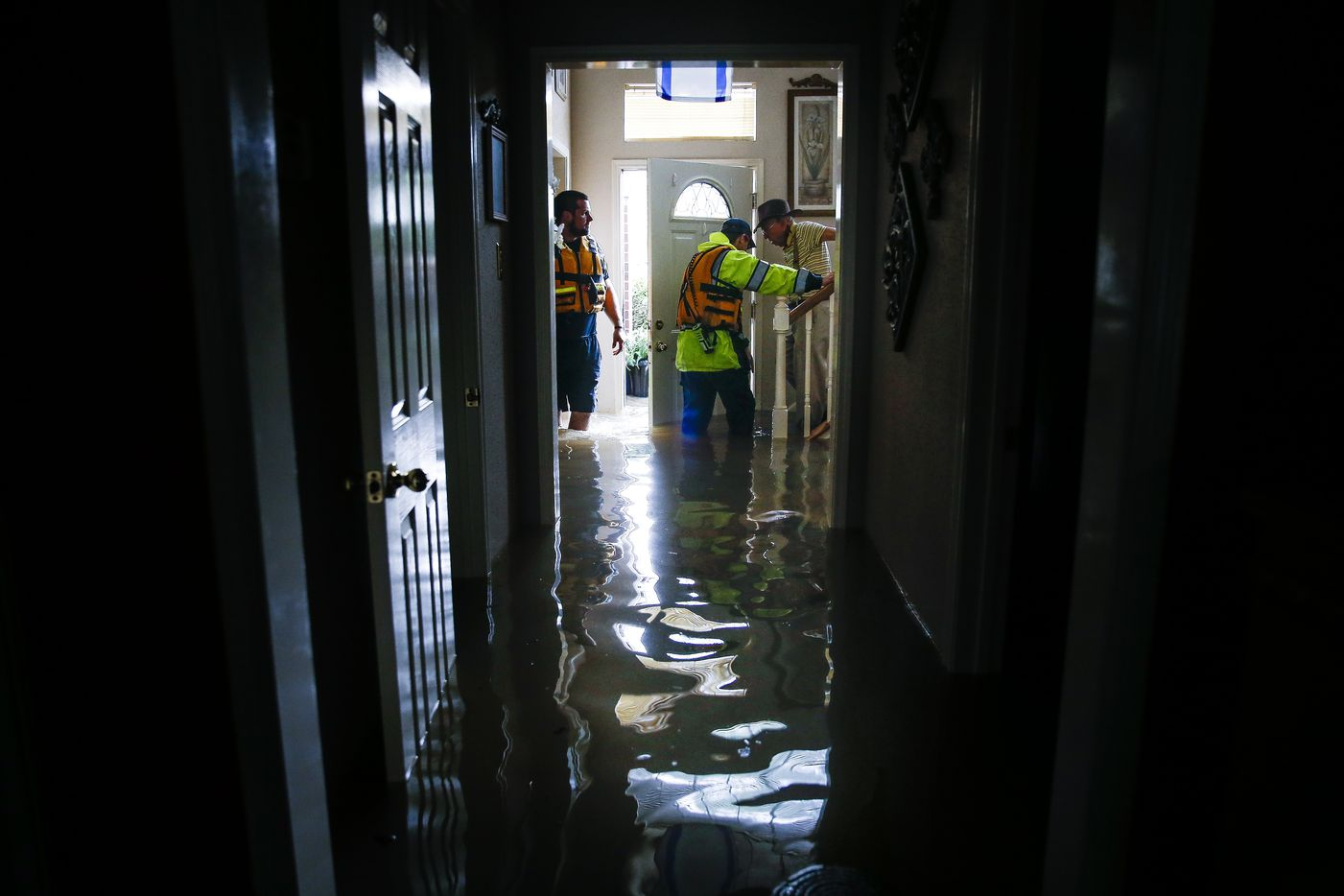 Cy-Fair volunteer firefighters help Ovidio Gutierrez down the stairs of their flooded house and into a waiting fire department truck in the Concord Bridge neighborhood as Addicks Reservoir surpasses capacity due to near constant rain from Tropical Storm Harvey Tuesday, Aug. 29, 2017 in Houston.