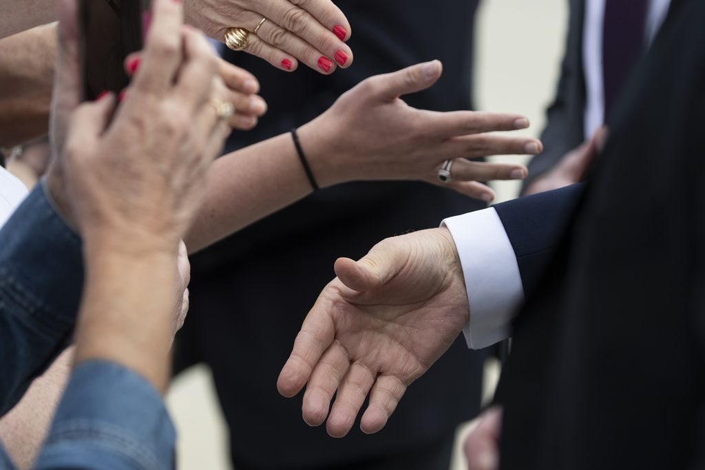 President Donald Trump, bottom right hand, shakes hands with supporters at Orlando Sanford International Airport in Florida on Monday, March 9, 2020.