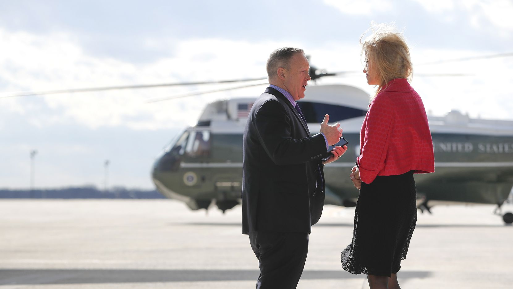 White House press secretary Sean Spicer, left, talks with Counselor to the President Kellyanne Conway, right, on the tarmac at Andrews Air Force Base. Md., at they wait for the arrival President Donald Trump, Thursday, Jan. 26, 2017.