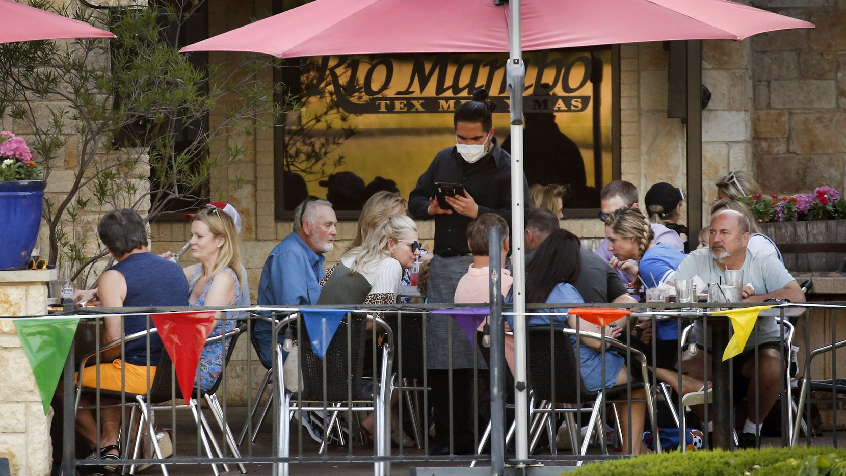 "On the first day of restaurants outdoor patios being reopened in Colleyville, Texas ""so long as physical distancing is maintained between tables,"" a waiter wearing a face mask takes orders from diners eating on the outdoor patio at Rio Mambo Tex Mex in Colleyville, Texas, Friday, April 24, 2020. As reopening continues, the city is now backing two programs to help small businesses in Colleyville promote themselves and bring back customers. (Tom Fox/The Dallas Morning News)"