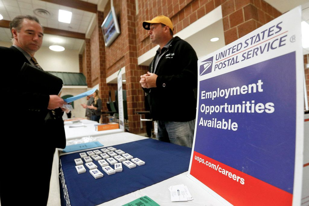 FILE- In this Nov. 2, 2017, file photo a recruiter from the postal service, right, speaks with an attendee of a job fair in the cafeteria of Deer Lakes High School in Cheswick, Pa.  Even with fear of a global economic slump depressing stock markets, Friday, Jan. 4, 2019 jobs report for December is expected to offer reassurance that the U.S. economy remains sturdy and on track to expand for a 10th straight year.  (AP Photo/Keith Srakocic, File)
