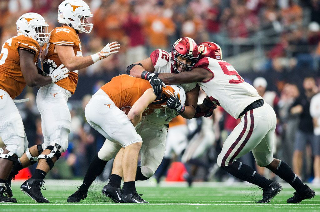 Texas Longhorns quarterback Sam Ehlinger (11) is sacked by Oklahoma Sooners cornerback Starrland Baldwin (12) and Oklahoma Sooners defensive lineman Kenneth Mann (55) during the second quarter of the Big 12 Championship football game between the Texas Longhorns and the Oklahoma Sooners on Saturday, December 1, 2018 at AT&T Stadium in Arlington, Texas. (Ashley Landis/The Dallas Morning News)