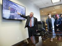 (From left) Attorney George Milner III shows the video of the incident as Kyle Vess the disabled homeless man who was kicked by Dallas Fire-Rescue paramedic Brad Cox in 2019, with sister Shelbi Madden and father Kevin Vess watch on Wednesday, Oct. 27, 2021, in Dallas. (Juan Figueroa/The Dallas Morning News)