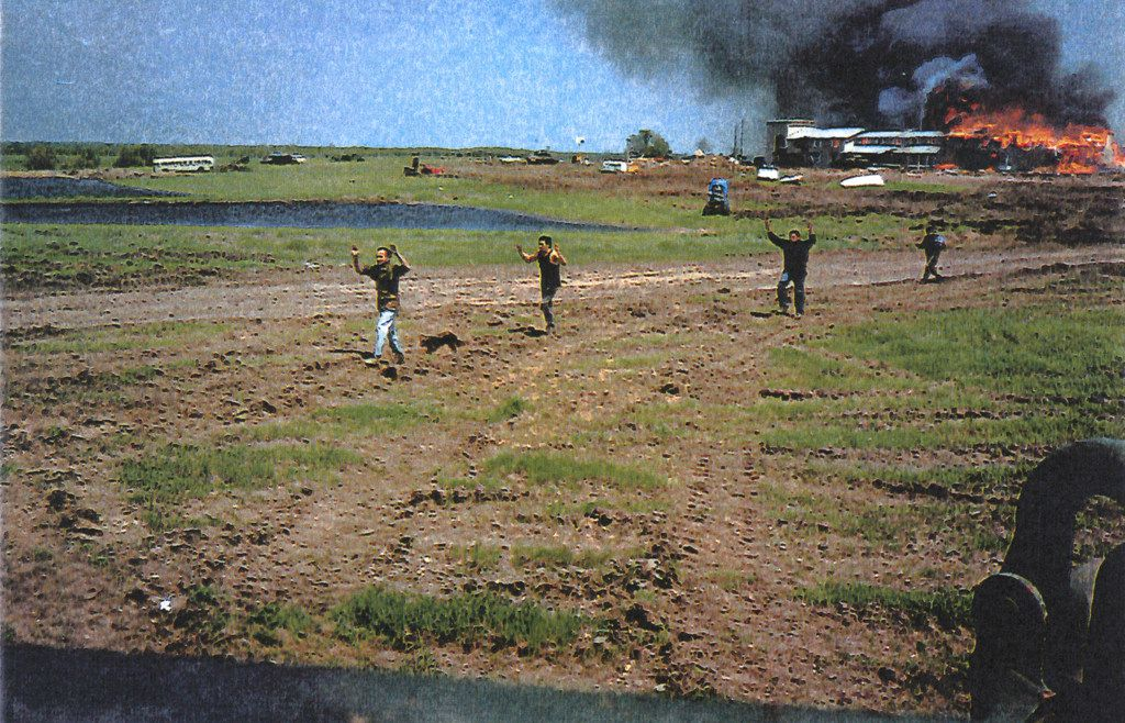 Survivors flee the burning building and approach a FBI Hostage Rescue Team position at the end of the standoff and siege of the Branch Davidian compound near Waco, Texas on April 19, 1993.