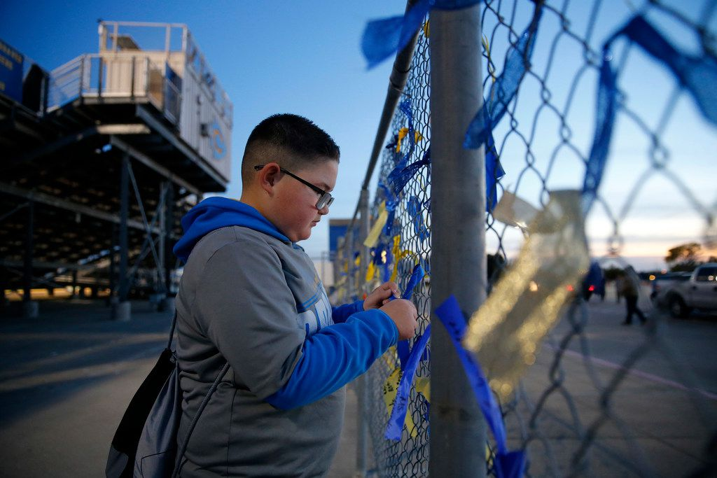 "Before the football game, fifth grader Justin Queneau ties a ribbon to the fence in the aftermath of the death of four Nevada Community students at Community ISD Stadium in Nevada, Texas, Friday, November 8, 2019. Justin added his message to the fence of condolences with the words, ""We miss you and love you"". The four high school students were killed earlier this week in a tragic vehicle accident. (Tom Fox/The Dallas Morning News)"