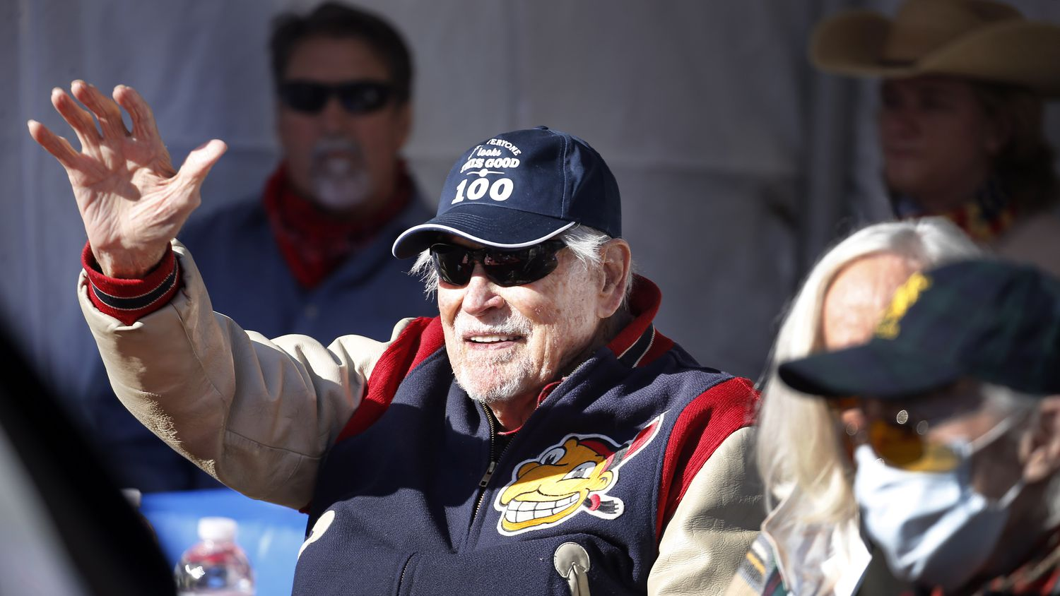 Eddie Robinson, the oldest living former MLB player, waves to friends who delivery an early 100th birthday wish. He will turn 100 on December 15th. To share his birthday with friends, his family orchestrated a drive-by celebration outside his Fort Worth home, Saturday, December 12, 2020. His 65 year career started by playing for the Cleveland Indians and serving in World War II. Later he went on to play for several other teams before presiding over three winning seasons as the Texas Rangers general manager. He is still in great physical health as he waves to passersby, including former teammates, GM Tom Grieve and U.S. congressman and neighbor Marc Veasey.