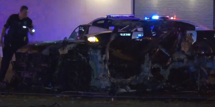 A Dallas police officer investigates the crash, which involved a Range Rover and Chevy Tahoe.