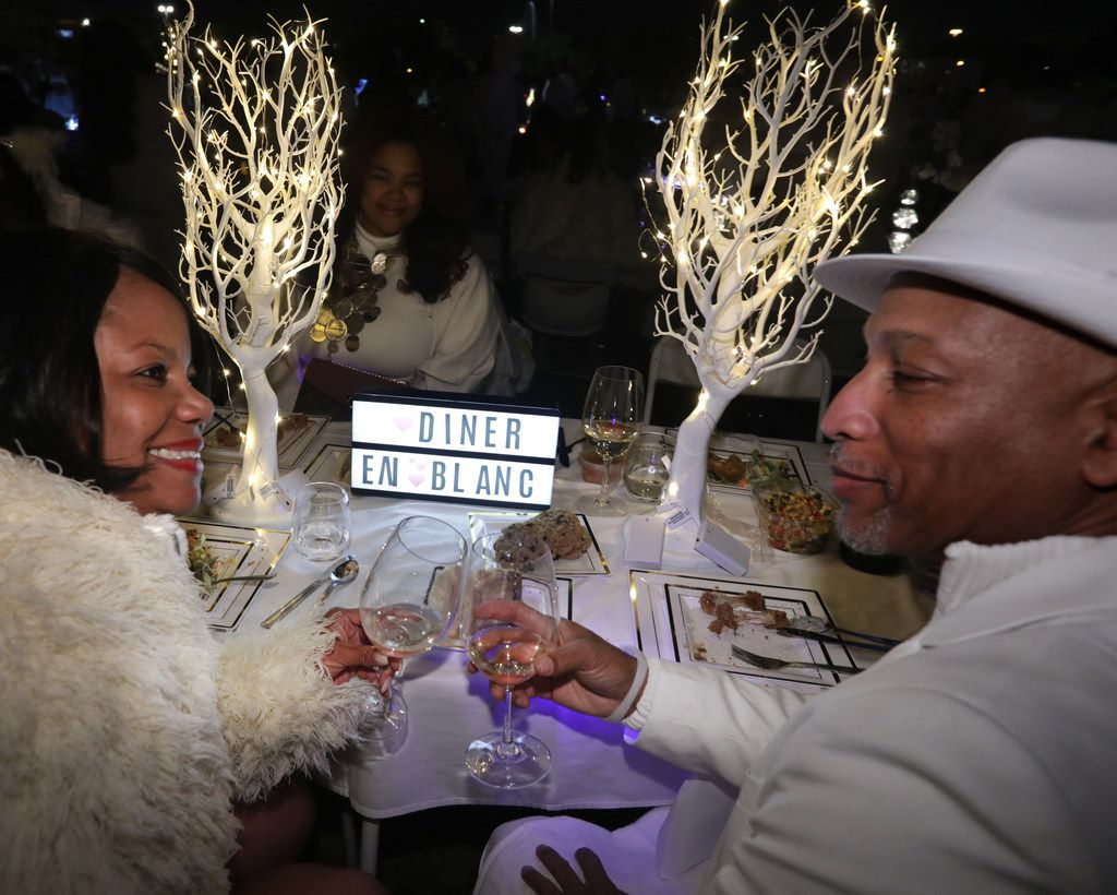 Serena Wright (left) and Levenis Wright toast during a secret Diner en Blanc event at Reunion Park in Dallas on Nov. 9, 2018.