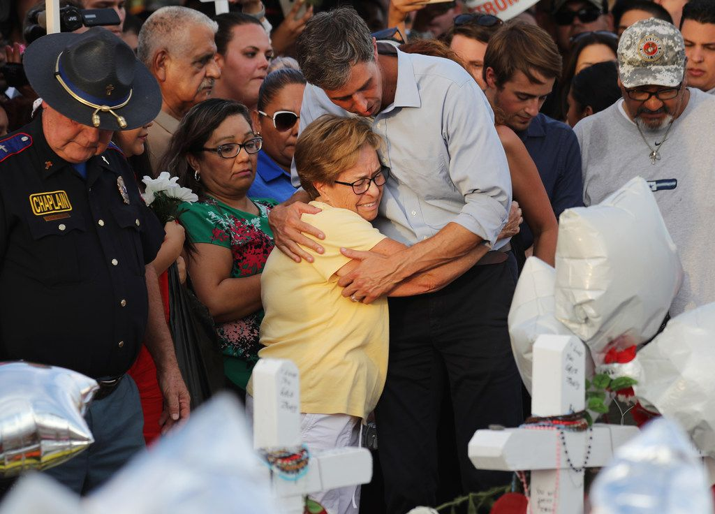 Democratic presidential candidate and former Rep. Beto O'Rourke hugs a woman at a makeshift memorial outside an El Paso Walmart on Aug. 7, after a mass shooting there that left 22 people dead.
