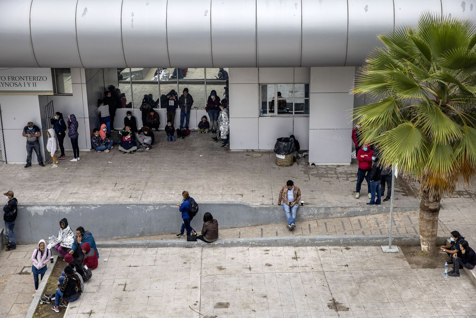 A couple dozen expelled migrant families sit in the plaza near the international bridge leading into the Mexican border city of Reynosa midmorning on Thursday, April 1, 2021.