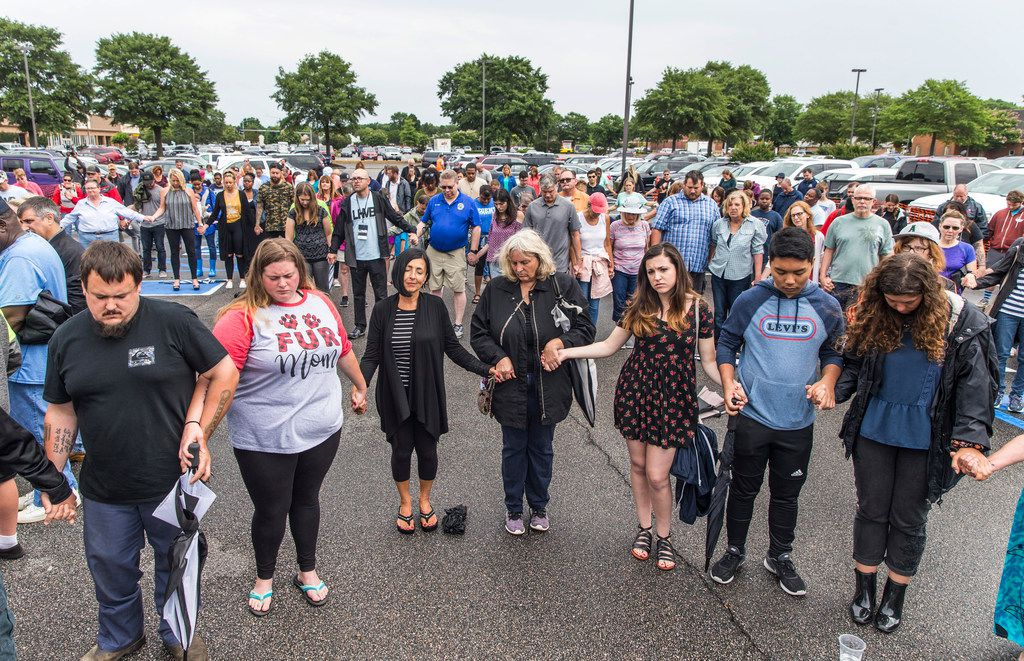 Participants pray together with holding hands during the prayer vigil at Strawbridge Marketplace in response to a shooting at a municipal building in Virginia Beach, Va., Saturday, June 1, 2019. A longtime city employee opened fire at the building Friday before police shot and killed him, authorities said. (Daniel Sangjib Min/Richmond Times-Dispatch via AP)