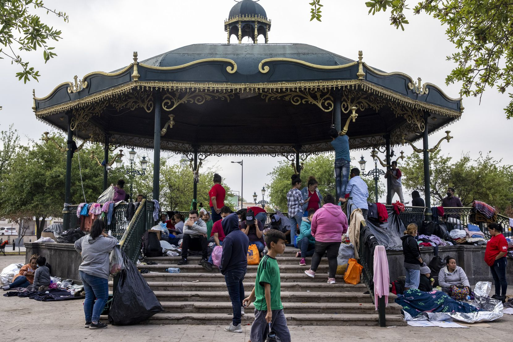 Expelled migrants mill around a gazebo in a public square in the Mexican border city of Reynosa. Migrants have resorted to living at the plaza as the U.S. continues to expel migrants under Title 42 — a pandemic-related public order still in place and left over from the Trump administration.