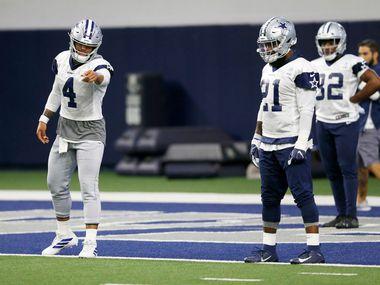 El mariscal de los Dallas Cowboys, Dak Prescott (4), habla con el el corredor Ezekiel Elliott (21) durante un entrenamiento del equipo en su campo de prácticas de Frisco, Texas