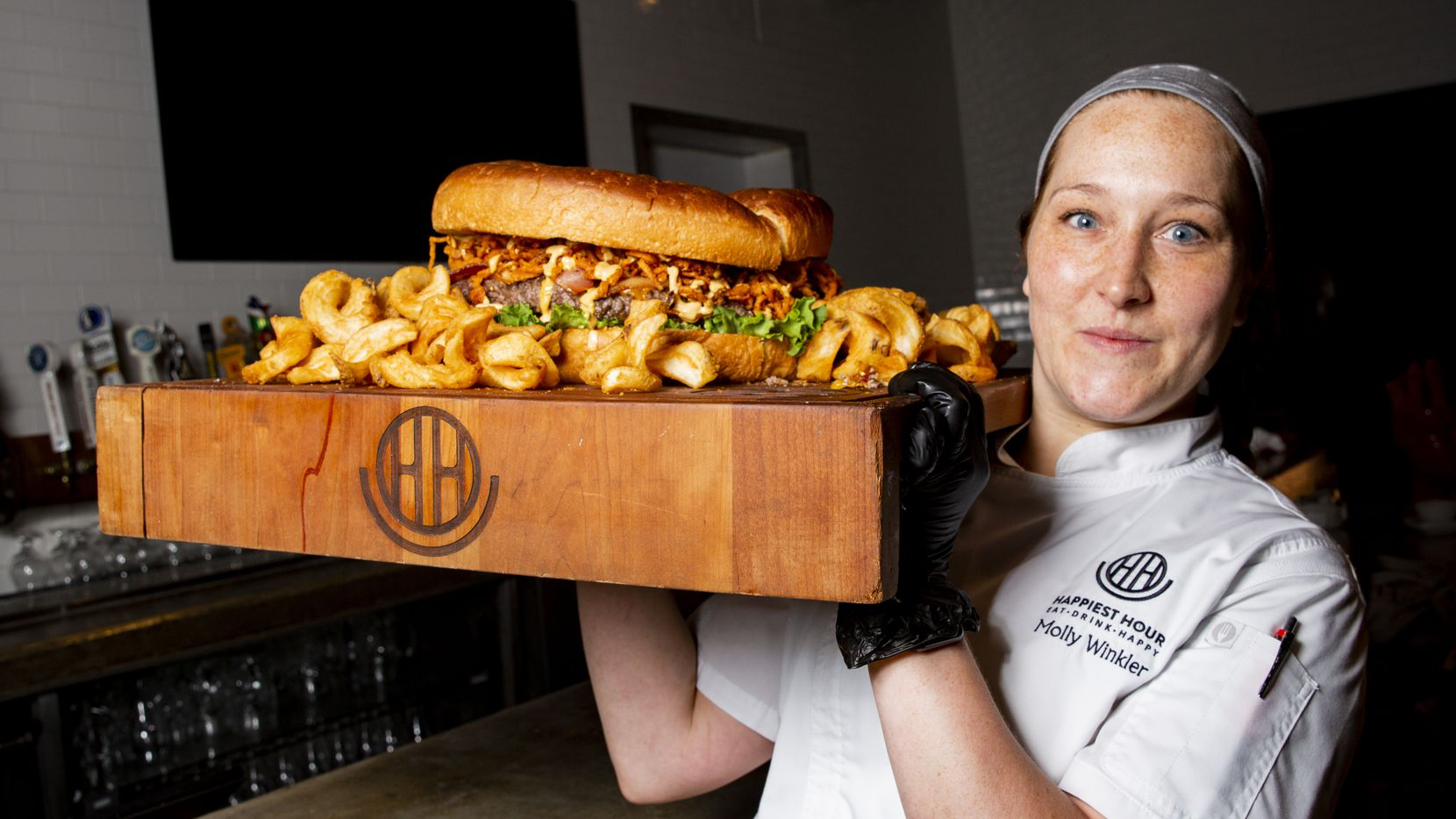 Executive chef Molly Winkler carries the 5-pound Big Happy Burger and 5 pounds of fries at Happiest Hour in Dallas. This cutting board is very heavy.