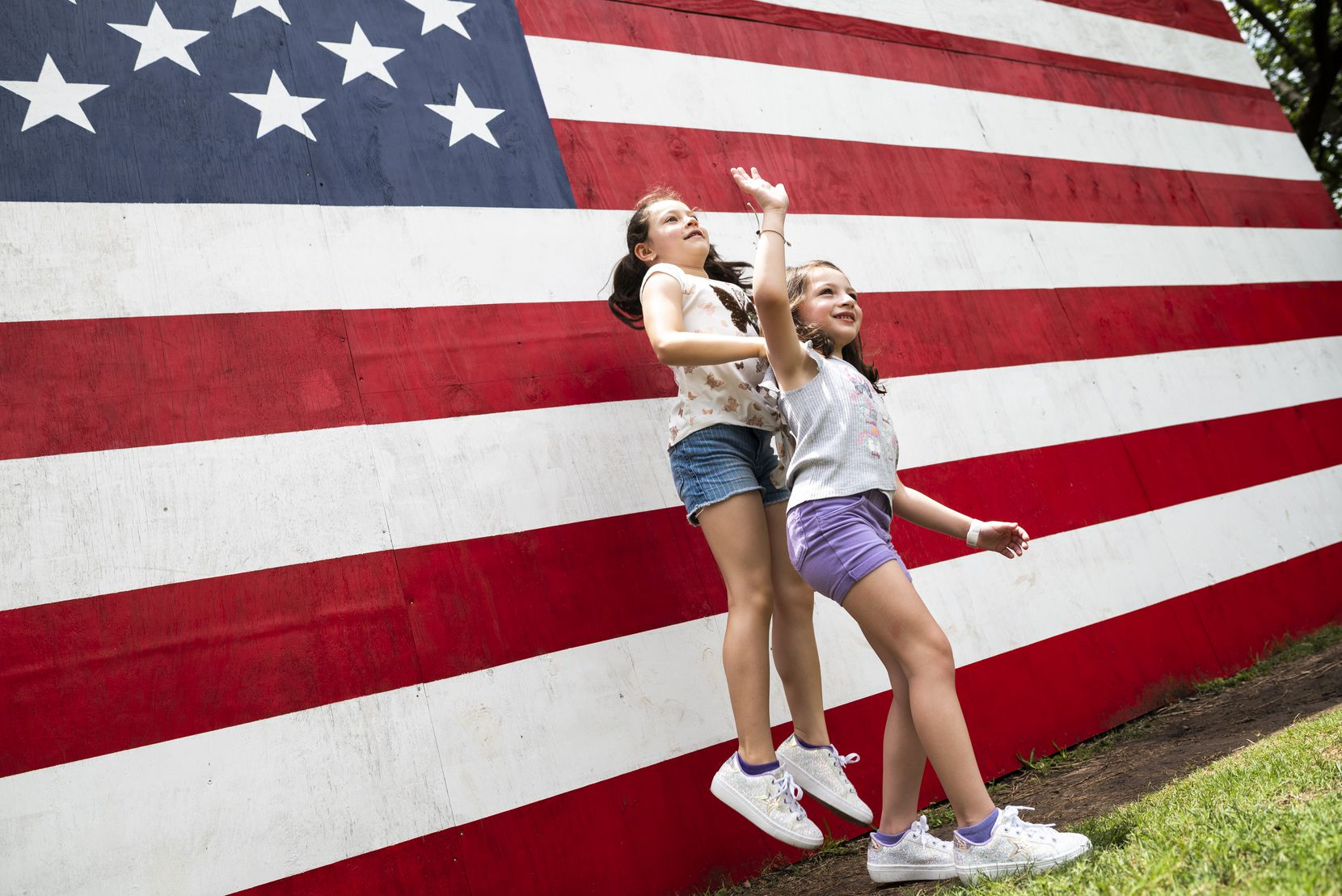Sisters Emori (left) and Harlow Smith posed while their mother grabbed a snapshot at the painted flag at the Dallas Arboretum.
