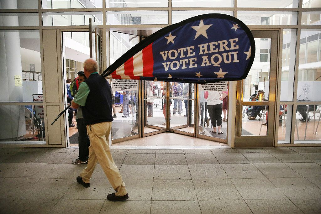 Election official Jimmy Murphy carried off a sign at the conclusion of Dallas County's early voting period on Friday at the George L. Allen Sr. Courts Building in downtown Dallas in 2012. (Andy Jacobsohn/Staff Photographer)