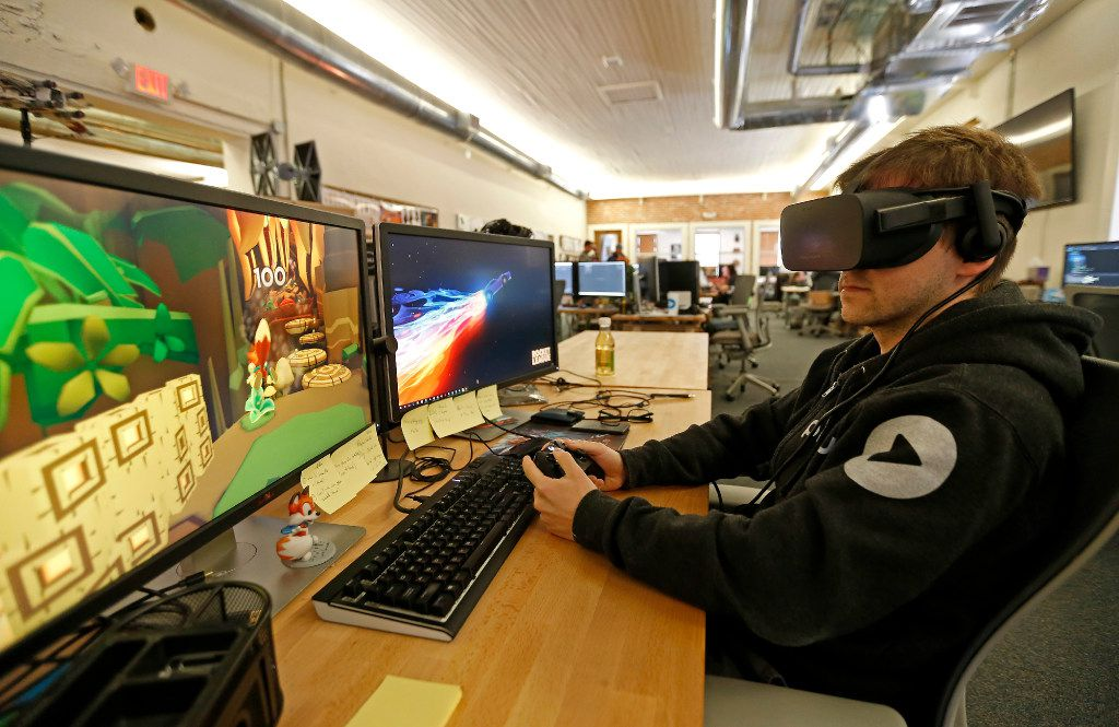 Software engineer Anthony Fleshner works at his desk as he wears a VR gear at Playful Corp. in McKinney.