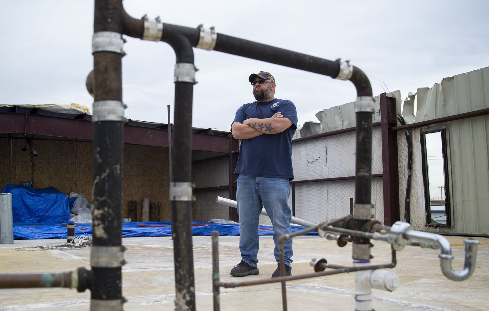 """Nick Edwards, owner of Star Tire, stands in the space that used to be his office. Today, he jokes, it's essentially """"an open-air deck"""" with a view of the ruins across Harry Hines Boulevard."""