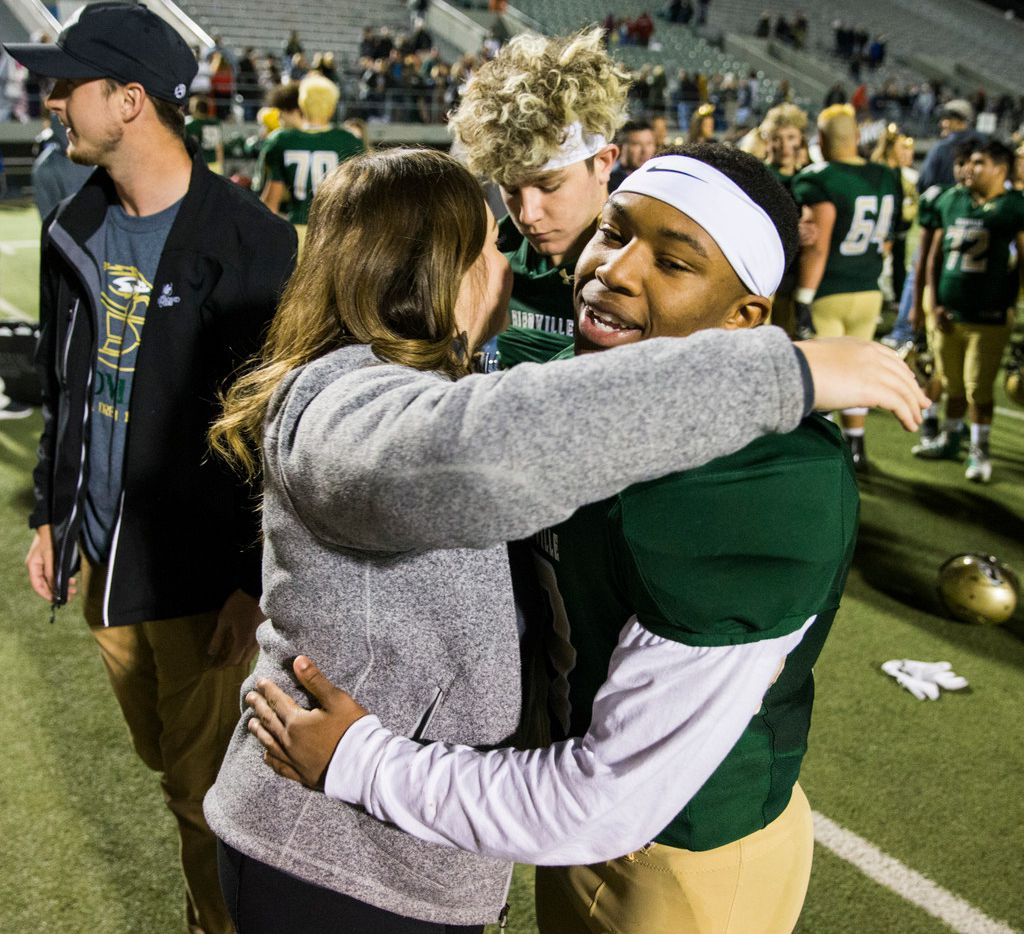 Birdville running back Laderrious Mixon (9) gets a hug from Ali Earle after a 29-27 win over Fort Worth Boswell on Thursday, November 15, 2018 at the Birdville Fine Arts Center in North Richland Hills, Texas. The Earle family, including quarterback Stone Earle (3), adopted Mixon. (Ashley Landis/The Dallas Morning News)