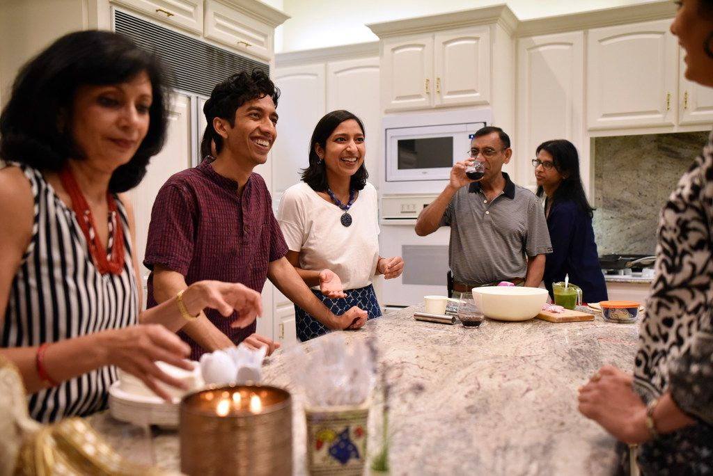Food writer and Dallas native Priya Krishna, third from right, speaks to family including mother Ritu Krishna, far-left, and cousin Hirsh Elhence, 24, as they prepare roti and paratha at her family's home in Dallas.