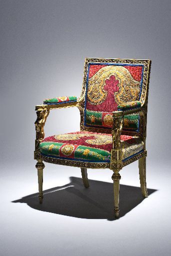 One of a pair of Empire-style armchairs clad in fabric given to Osborn by fashion legend Gianni Versace that was auctioned off in 2009.