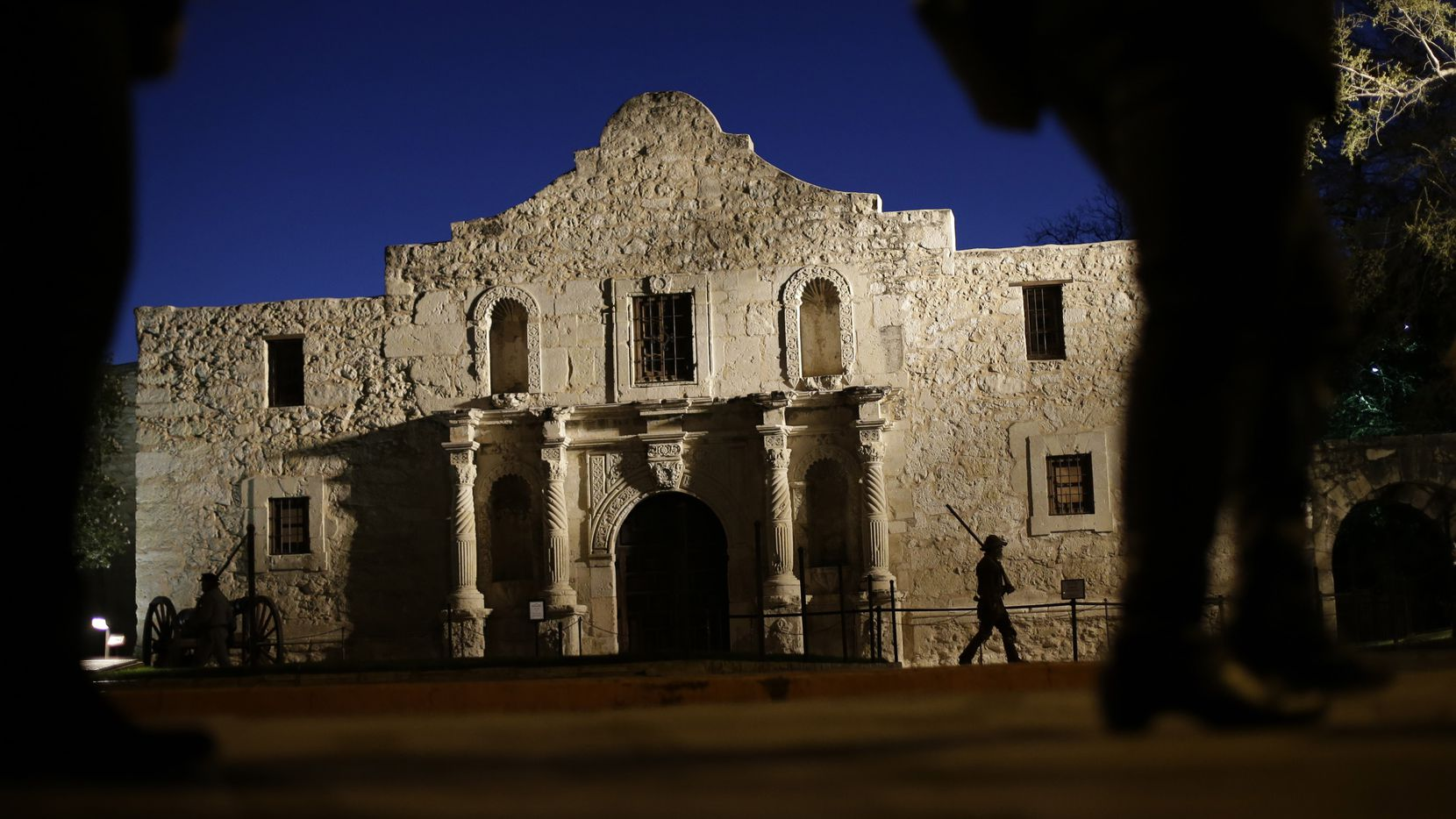 In this March 6, 2013, file photo, Dan Phillips, a member of the San Antonio Living History Association, patrols the Alamo during a pre-dawn memorial ceremony to remember the 1836 Battle of the Alamo and those who fell on both sides, in San Antonio.