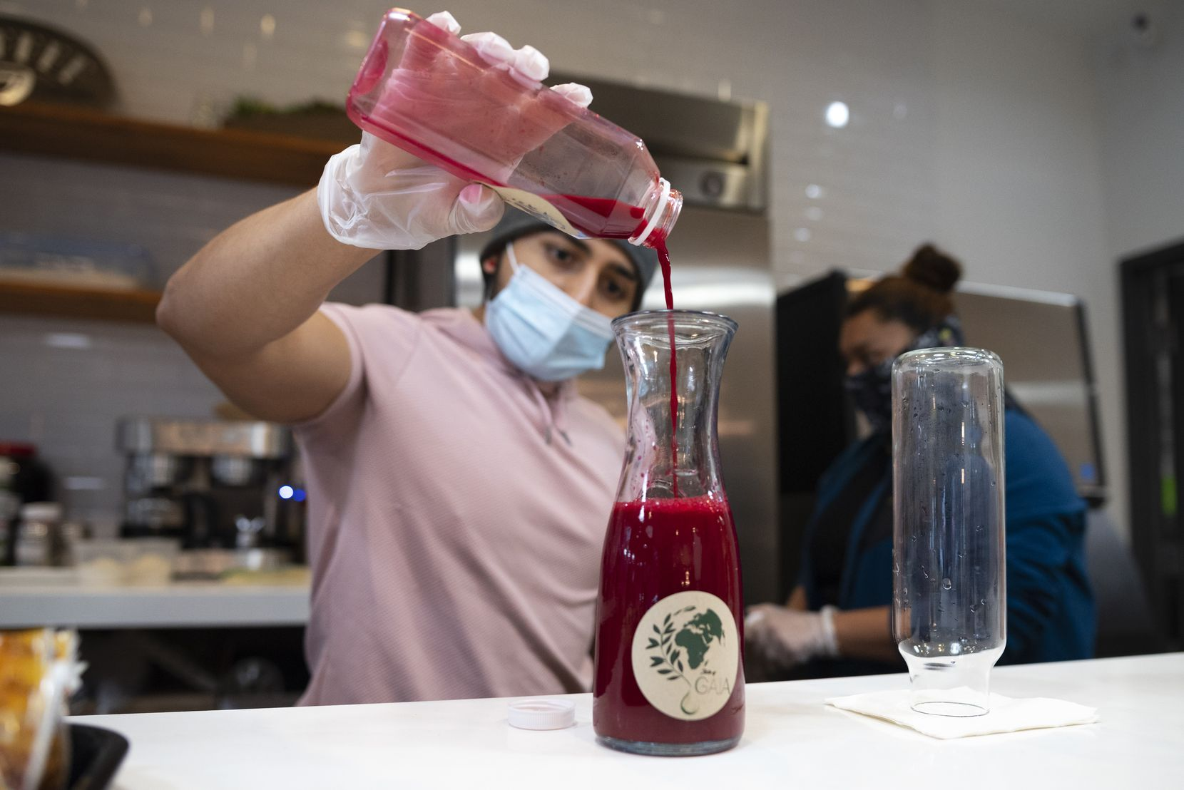 Partner Angel Diaz pours an Apollo juice into a serving bottle at the juice bar inside Taste of Gaia in downtown Dallas, on Wednesday, Dec. 31, 2020.