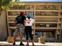 Protestors Xavier Reyes and his girlfriend, Aprille Peterson, raise their Black Lives Matter painting toward Dallas City Hall during a silent protest Thursday. Peterson is wearing Xavier's Colin Kaepernick jersey, one he got before the NFL quarterback's kneeling protest and has worn ever since.