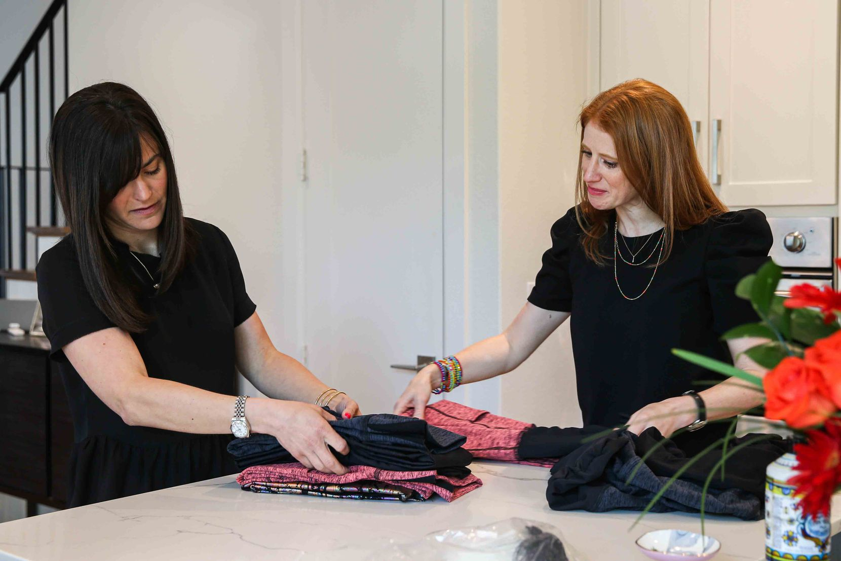 Loren Heller and Hillary Cullum fold their Berkley Clothing maternity workout leggings at their home office/work studio in Dallas.