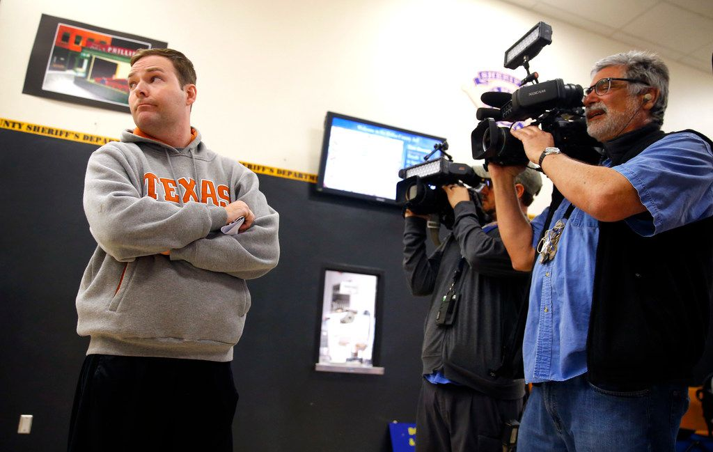Austin Shuffield, 30, looks away from cameras as he waits for a ride at the Dallas County Jail after being released on a $1000 bond from the jail, Friday, March 29, 2019.  Shuffield was booked into the Dallas County Jail about 8:15 a.m. Friday on an unlicensed-weapon charge, one of four misdemeanors he faces, along with assault, interfering with an emergency call and public intoxication. The latest arrest warrant for Shuffield reveals that police believe he pulled out a gun during his argument with L'Daijohnique Lee, just before the March 21 fight.