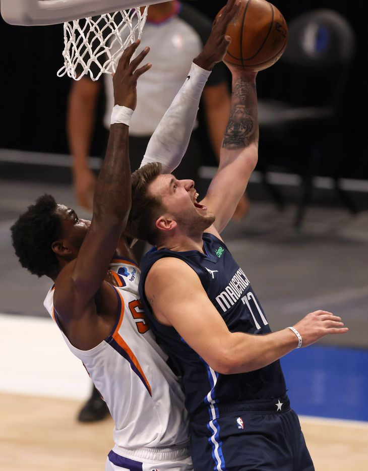 Dallas Mavericks guard Luka Doncic (77) attempts a shot in front of Phoenix Suns center Deandre Ayton (22) during the first quarter of play at American Airlines Center on Monday, February 1, 2021in Dallas. (Vernon Bryant/The Dallas Morning News)