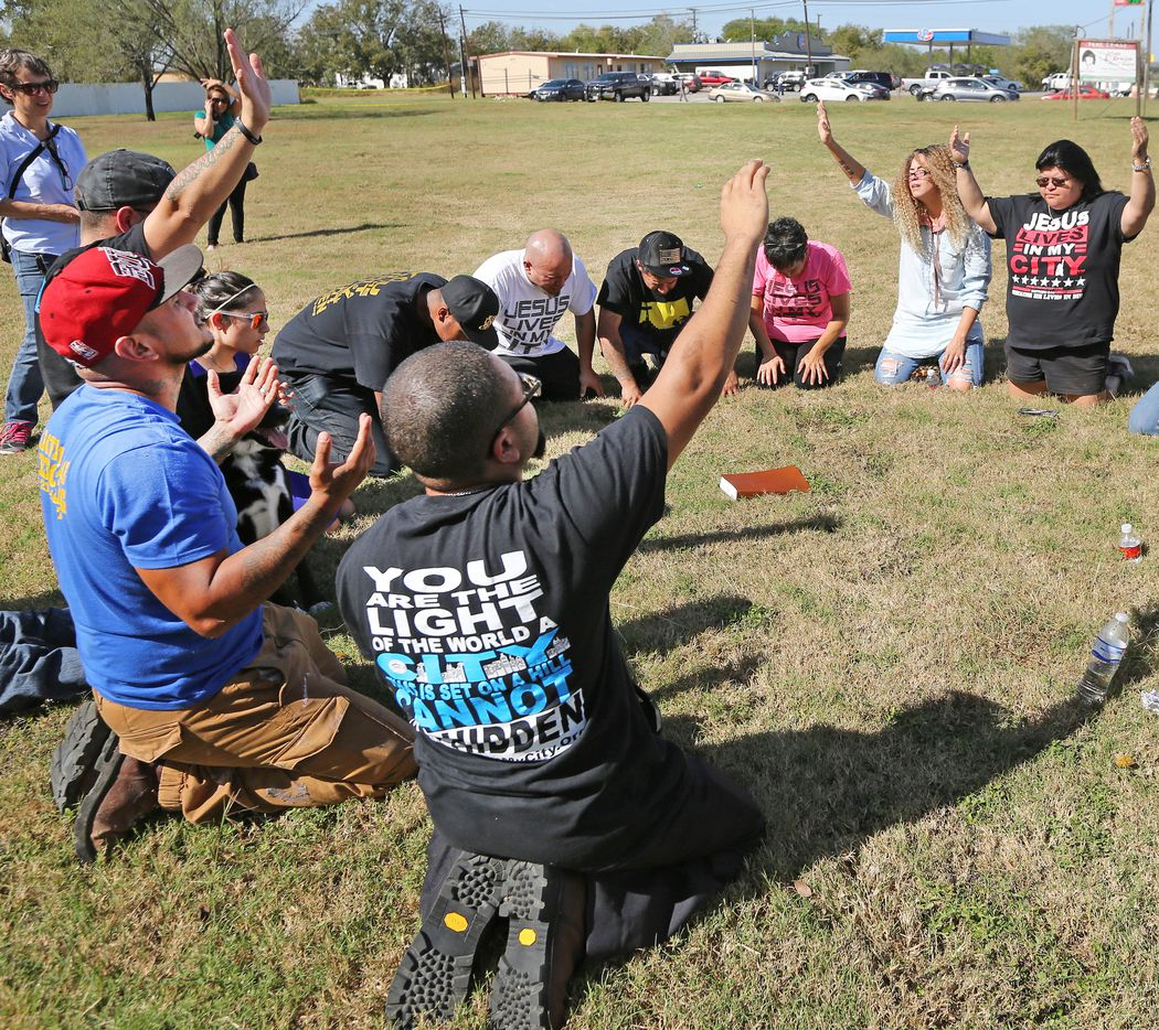 People pray in a field near the First Baptist Church of Sutherland Springs.