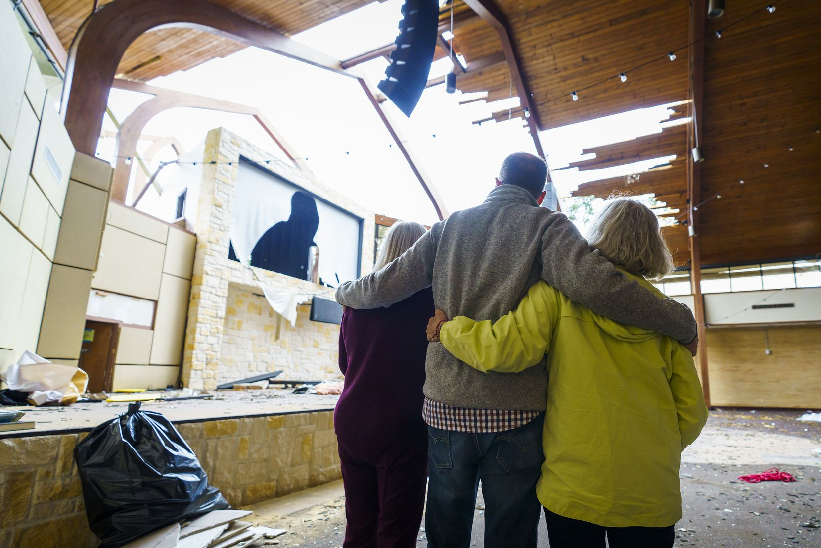 Northway Church lead pastor Shea Sumlin offers comfort to KC Pemberton, left, and Sonie Monroe, who had not seen the damage to the sanctuary until Thursday afternoon.