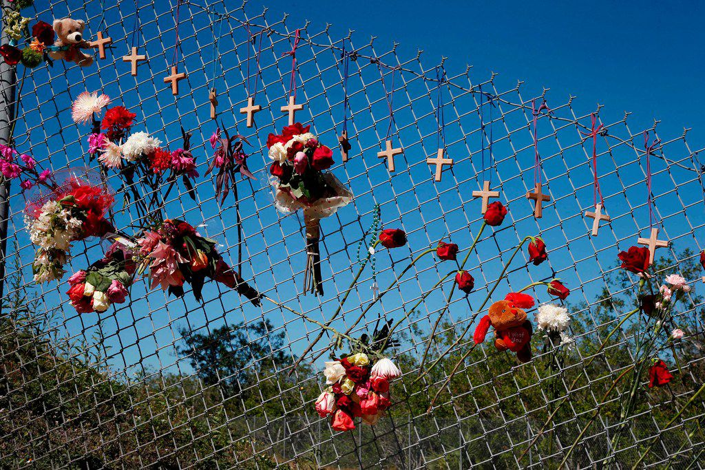Flowers and crosses line a fence near the school on a makeshift memorial for the victims of the Marjory Stoneman Douglas High School shooting in Parkland, Fla., on Feb. 14.