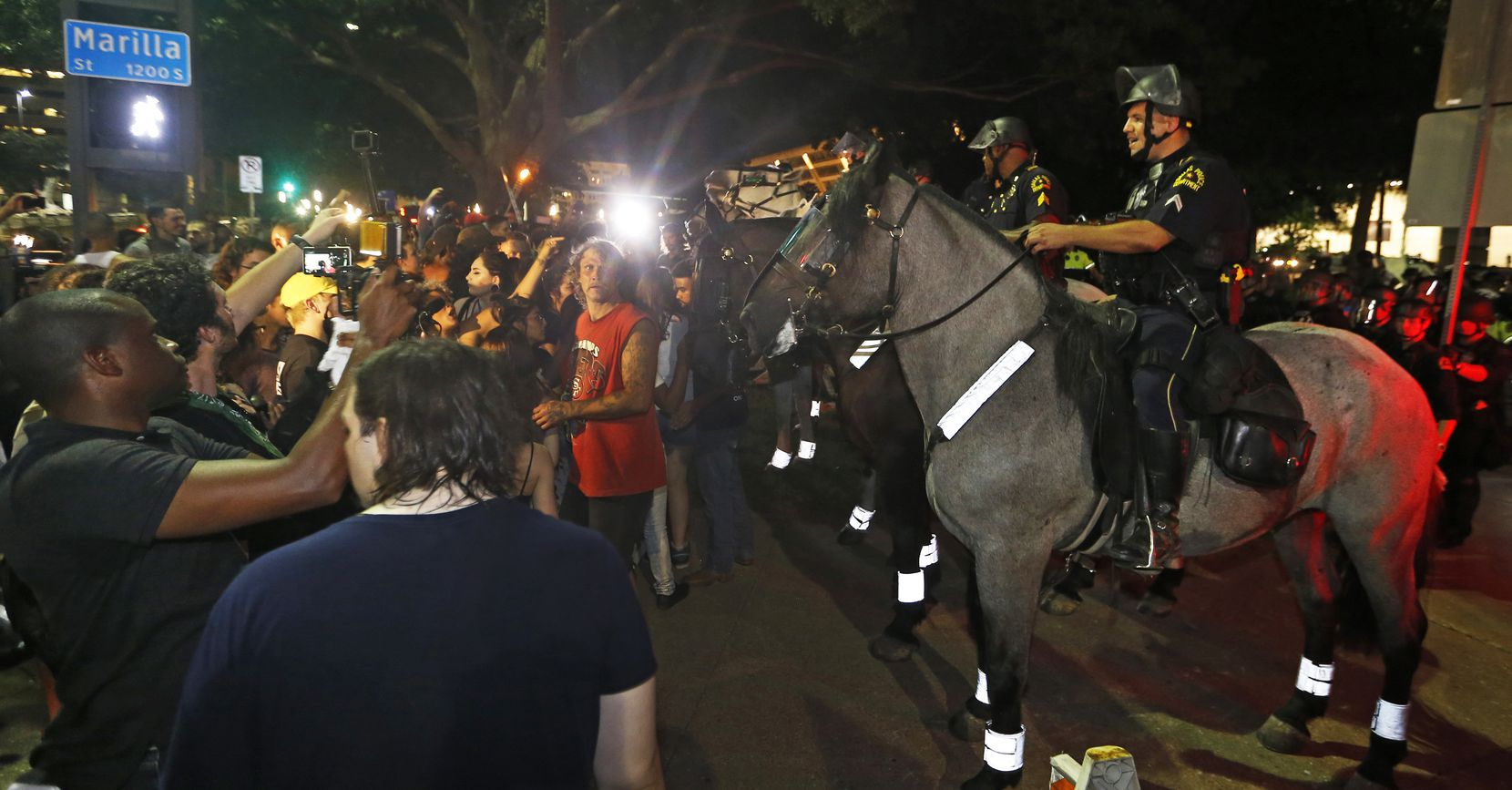 A line of police on horses push protestors back to Young Street after the March Against White Supremacy.