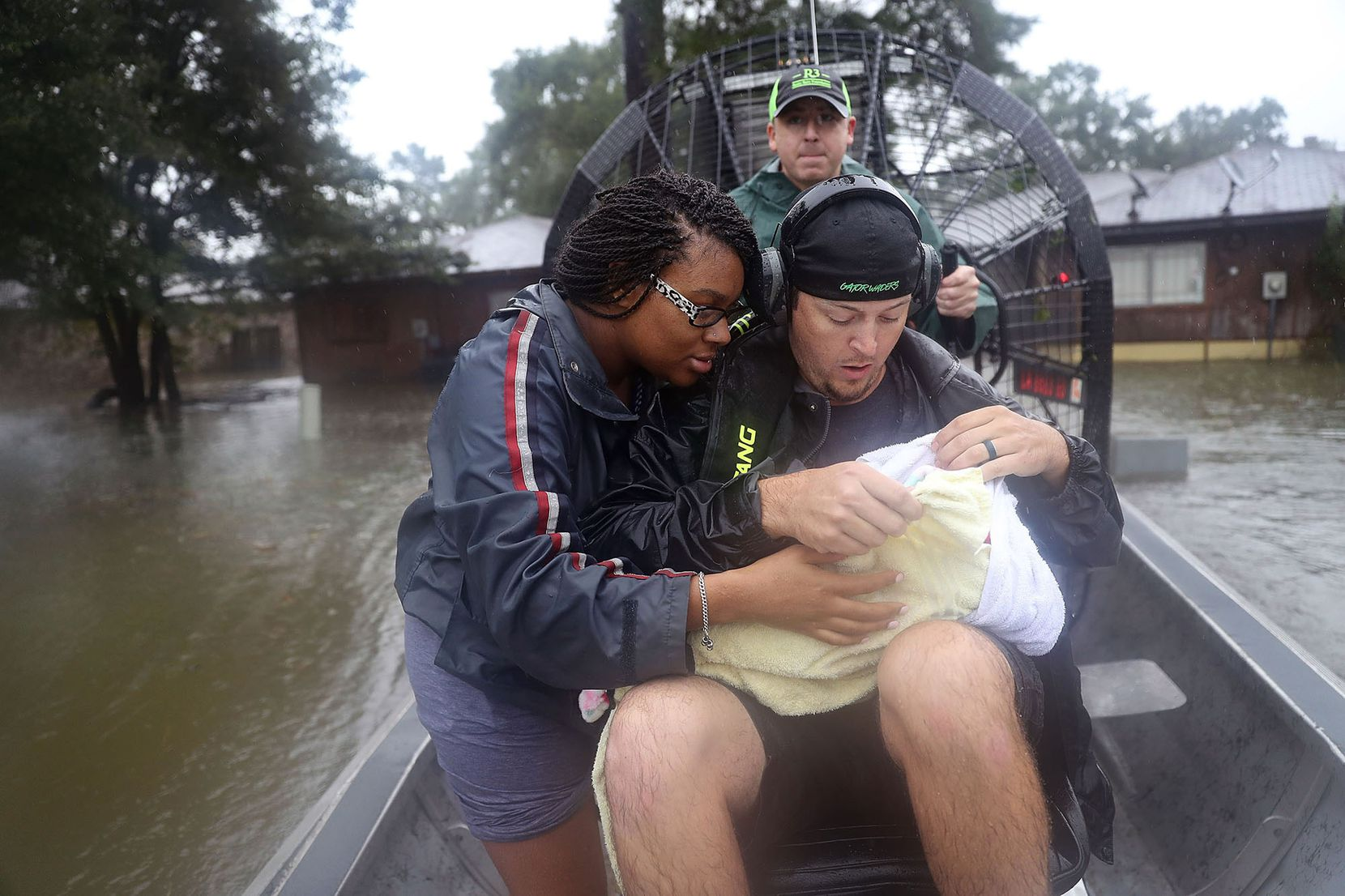 Shardea Harrison looks on at her 3 week old baby  Sarai Harrison being held by Dean Mize as he and Jason Legnon used his airboat to rescue them from their home after the area was inundated with flooding from Hurricane Harvey on August 28, 2017 in Houston, Texas.
