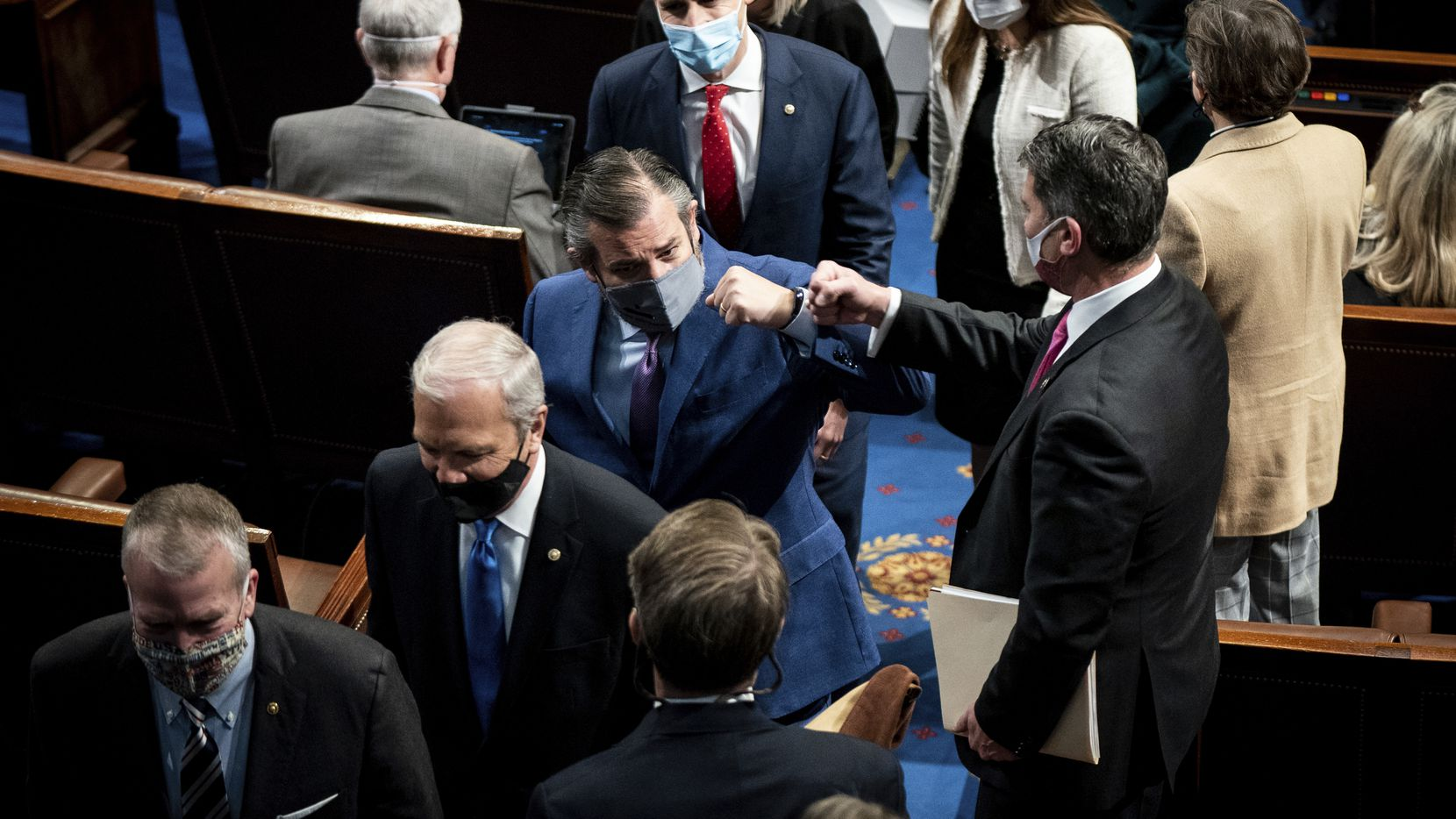 Sen. Ted Cruz, R-Texas, fist bumps with a House member as he leaves as a joint session of the House and Senate, as Congress convened to confirm the Electoral College votes cast in November's election on Jan. 6, 2021.