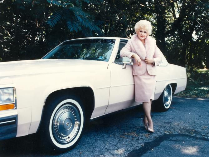 Mary Kay founder Mary Kay Ash stands next to one her iconic pink Cadillac Fleetwoods.