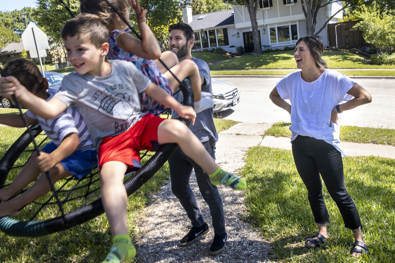 Ryan and Taylor Hollingshead play with their children (from left), their 2-year-old foster son, 4-year-old son Huck and 3-year-old daughter Quinn, on a circular swing at their home in Richardson.