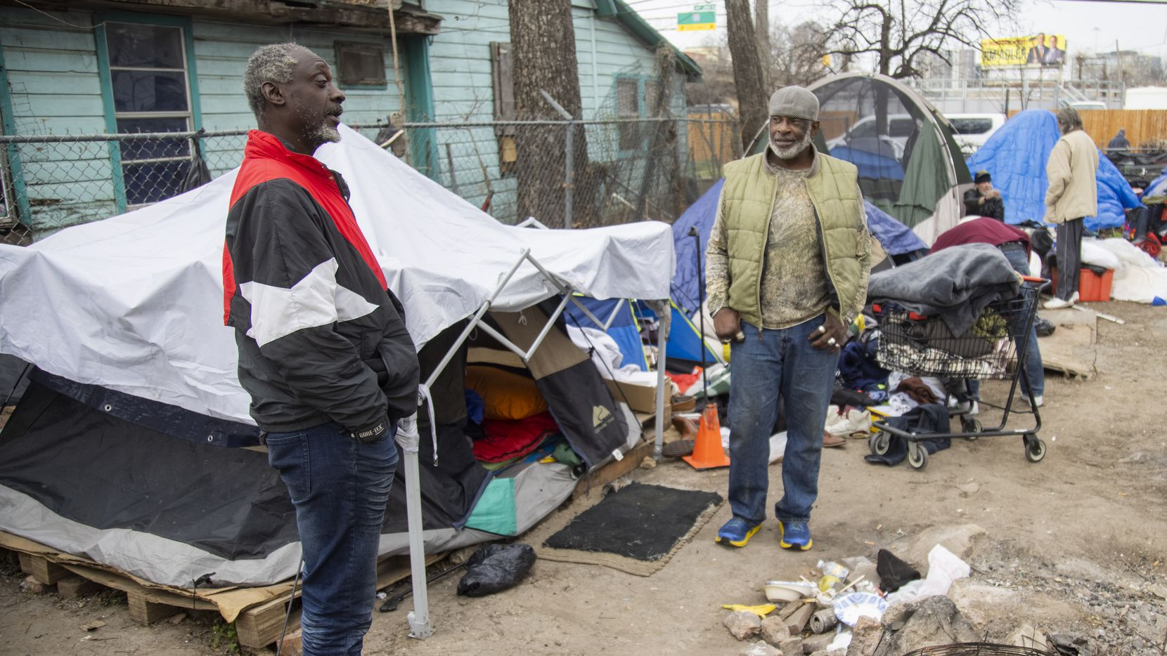 Melvin Hunter (left) chats with Andre Collins at Camp Rhonda, a homeless encampment located on a lot along Interstate 45, on Feb. 5, 2021 in South Dallas. City officials sent a notice to the owner of the property, Johnny Aguinaga, that the lot needed to be empty by Feb. 6.